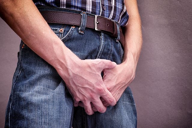 man's hands covering his boner