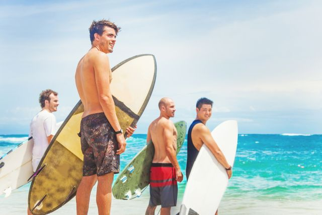 A group of male surfers standing by the sea