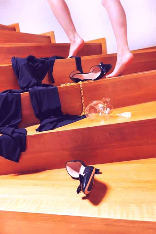 shoes, dress and a glass of wine empty lying on the stairs