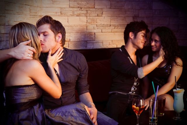 Two guys pulling girls on the couch of a nightclub