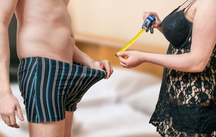 woman measuring the penis of her man