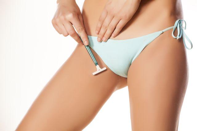 Girl in a bikini is shaving her crotch