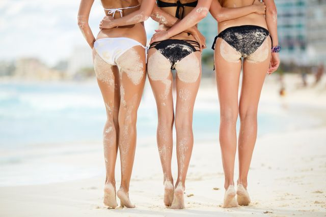 Three sexy female butts in bikini slips and covered in sand