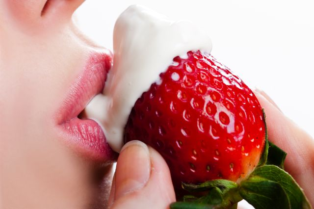 Female mouth licking cream off a strawberry