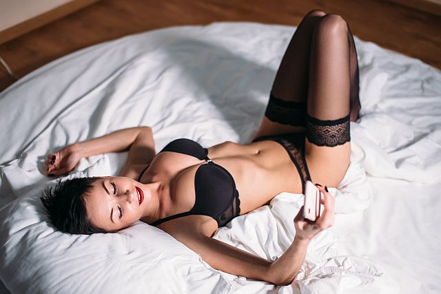 woman in lingerie lying on a bed with a mobile phone