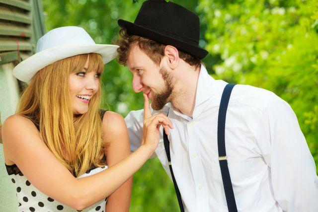 girl playfully shushing the man flirting with her