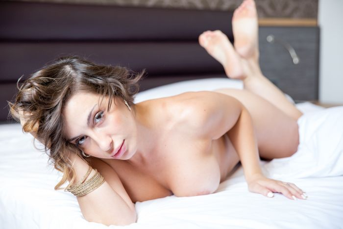 Horny woman lying naked on bed