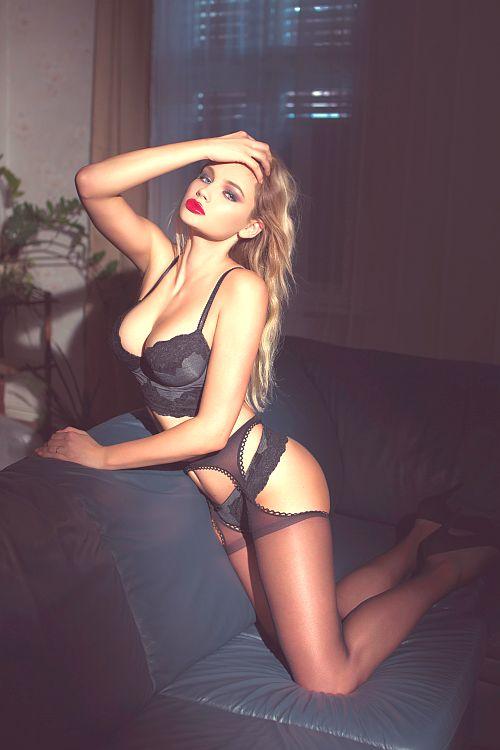 radiant blonde girl kneeling on a sofa