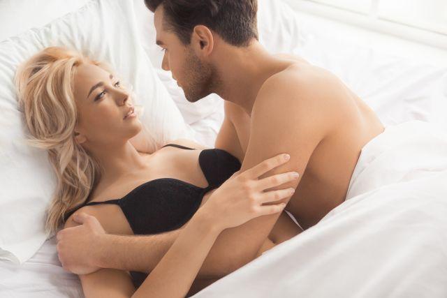 Kvinne og mann i sengen ser på hverandre