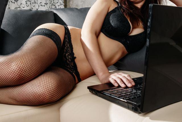 Frau in Reizwäsche arbeitet an ihrem Laptop