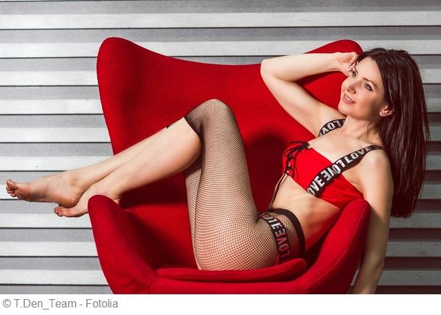 Frau ist ausgefallender Kleidung sitzt seitlich auf einem roten Sessel