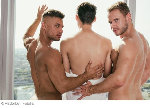 3 schwule Männer stehen am Fenster