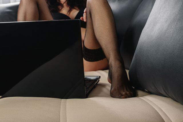 sexy Frau liegt mit Notebook auf Bett