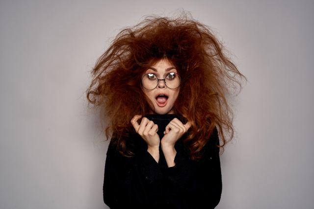 Frau mit stark toupierten Haaren und großer Brille