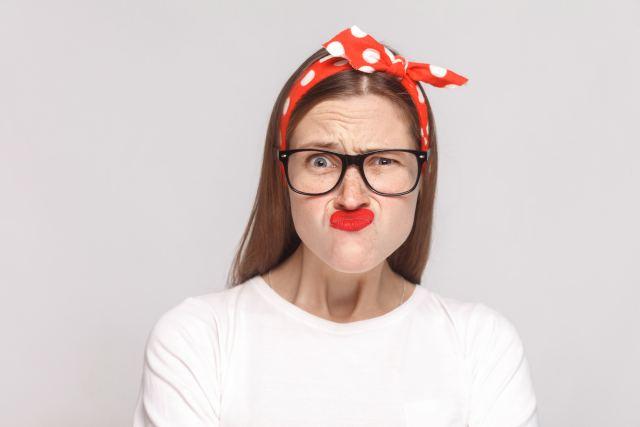 Frau mit rotem Haarband verzieht ihr Gesicht