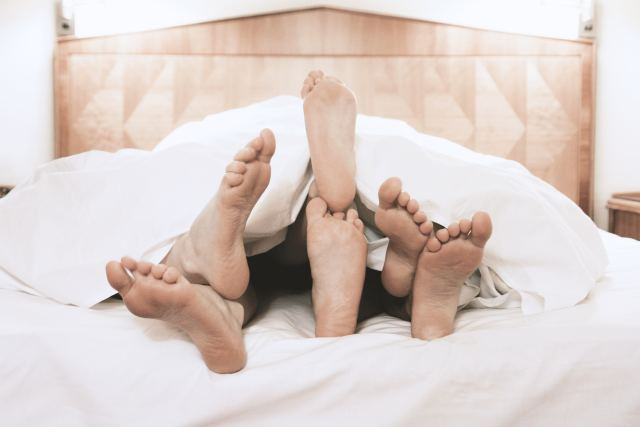 3 Paar Füße gucken unter einer Bettdecke hervor