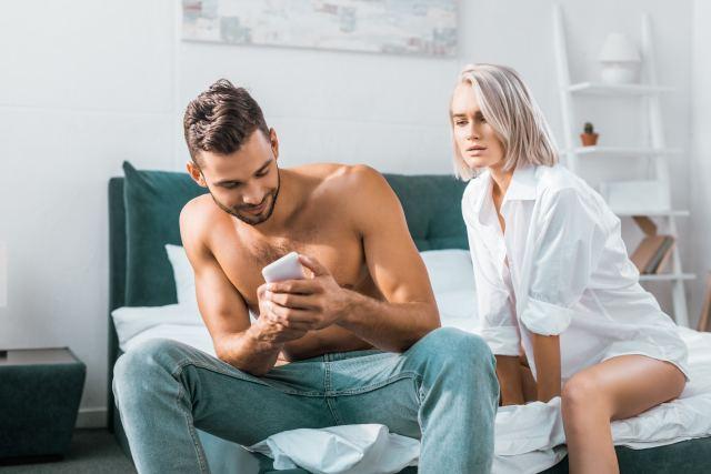 Frau schaut Partner über die Schulter auf sein Phone