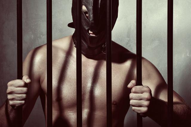 Mann mit Fetischmaske hinter Gittern