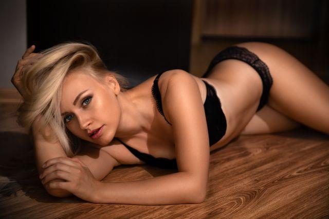 sexy Blondine posiert auf Holzdielen