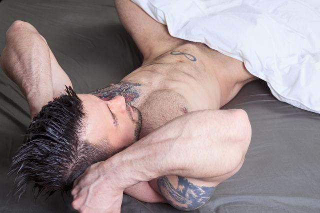 tätowierter Mann räkelt im Bett