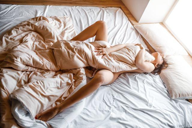 Frau hält Bettdecke zwischen ihren gespreizten Beinen