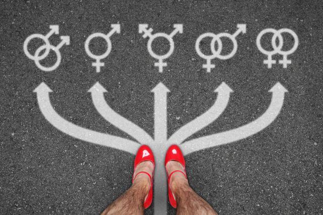 Männerfüße in High Heels vor allen Gender-Symbolen auf Straße gemalt