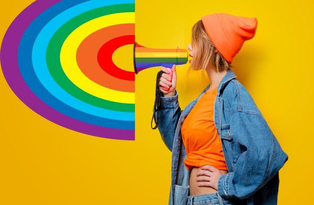 Frau mit Megaphone in Regenbogenfarben vor gelbem Hintergrund