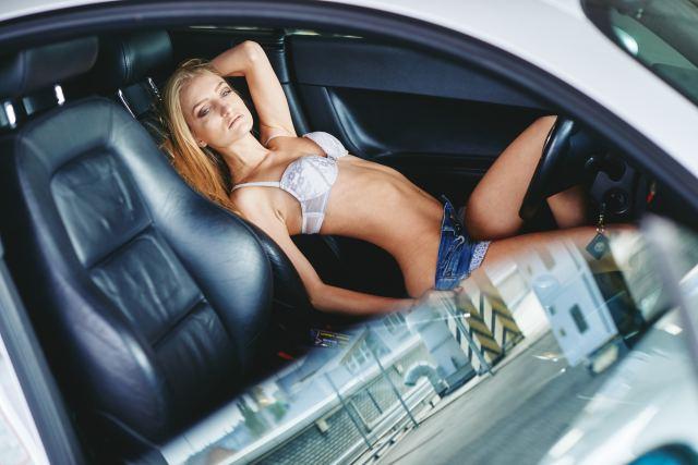 Frau zieht sich im Auto aus