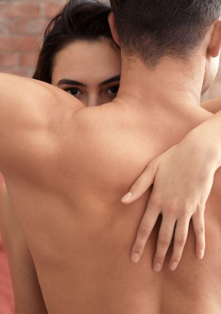 Frau blickt Mann mit nacktem Oberkörper über die Schulter