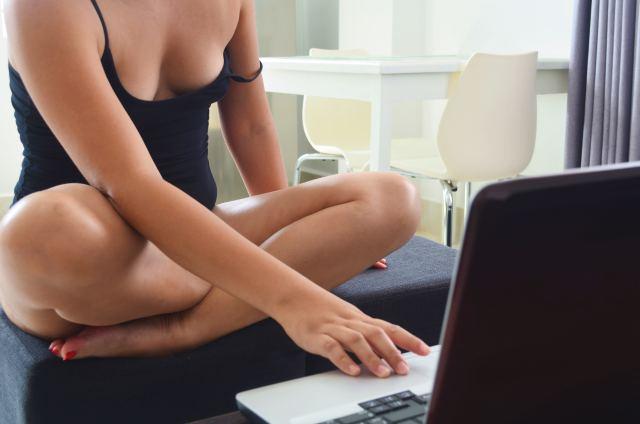 Frau in schwarzem Hemd sitzt leger vor Laptop