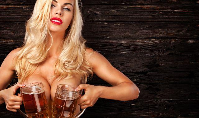 sexy Blondine hält sich zwei Bierkrüge vor die nackten Brüste