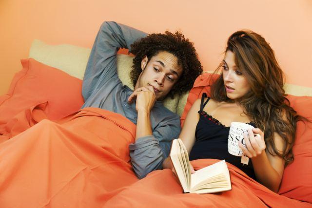 Mann präsentiert seiner Partnerin seine Erektion unter der Decke