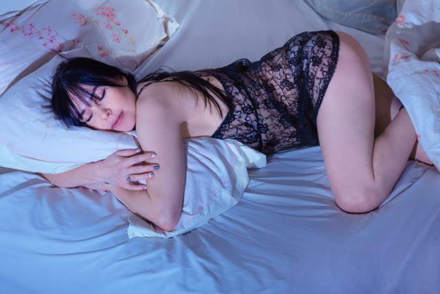 Frau umklammert im Schlaf ihr Kissen