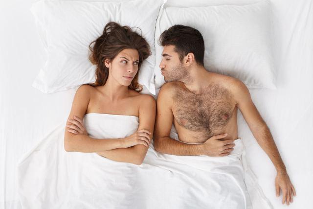 Mann schürzt Lippen zum Kuss in Richtung seiner Partnerin