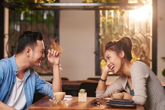 Asiatisches Paar sitzt fröhlich am Tisch