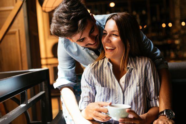 Mann umarmt Frau mit Kaffeetasse von hinten