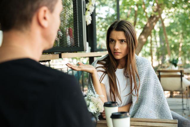 Frau sieht ihren Gesprächspartner vorwurfsvoll an