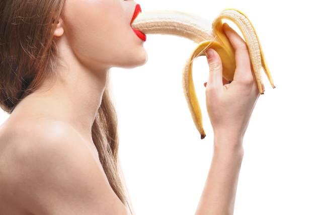 Frau schiebt sich Banane in den Mund