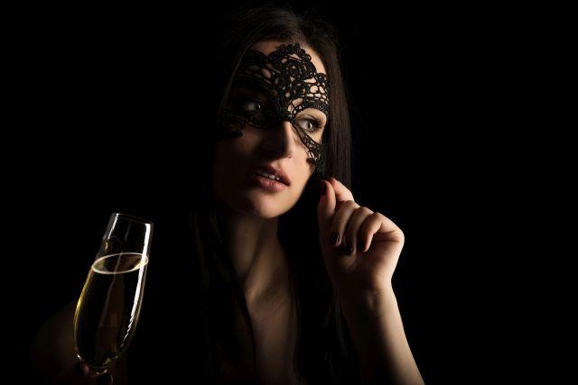Frau verbirgt ihr Gesicht hinter Maske aus Spitze