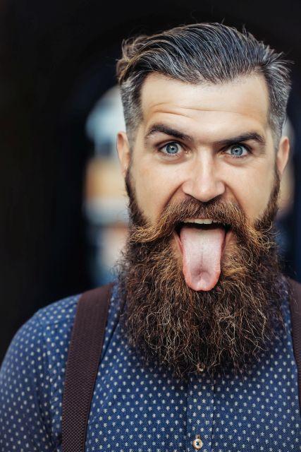 Hipster mit Bart streckt Zunge raus