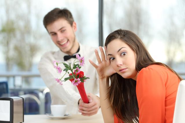 Mann hält Frau Blumenstrauß hin, sie wendet sich peinlich berührt ab