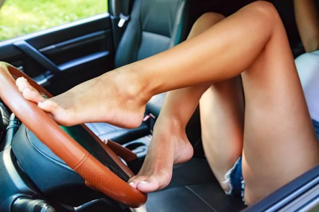 Nackte Frauenbeide auf stützen sich auf Lenkrad ab