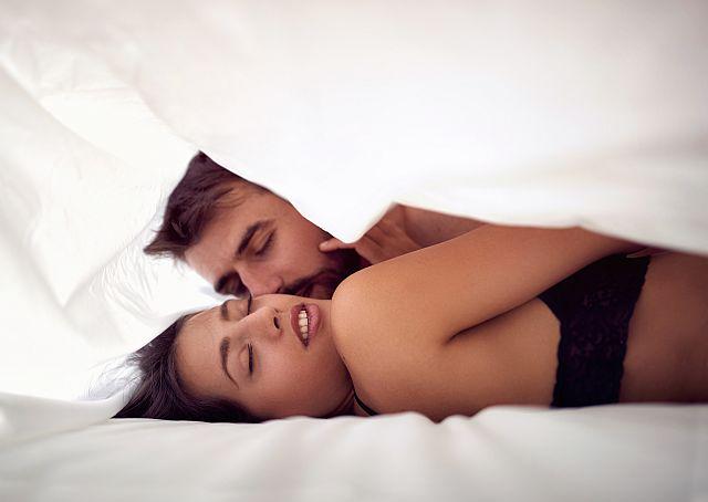 Leidenschaftliches Paar unter einer Bettdecke
