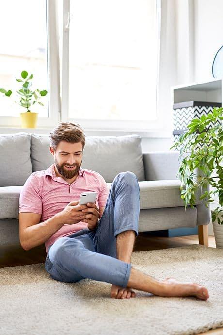 Mann sitzend auf dem Boden mit Smartphone