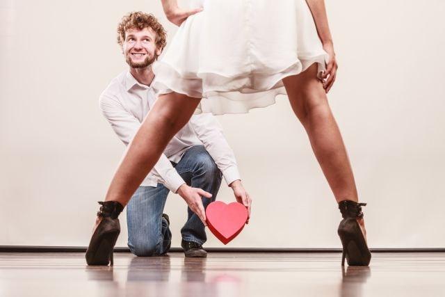 Mann bietet herzförmige Schachtel seiner breitbeinig-stehenden Frau an
