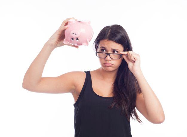 Frau schaut ernst leeres Spaarschwein an