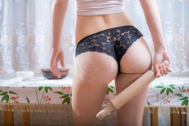 Frau präsentiert ihren Hintern und hält dabei Nudelholz