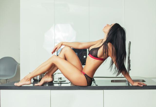 junge Frau posiert in Reizwäsche auf Küchenanrichte