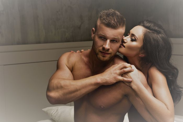 Hot naked man with woman kissing him on the bed