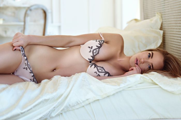 Hot woman in pink underwear lying on bed